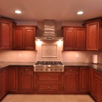 Cherry cabinets with decorative stone back splash and stainless steel appliances