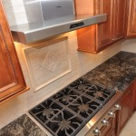 Kitchen Stove and Hood with decorative stone tile backsplash