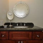 Bathroom cherry cabinets with green granite counter top and decorative mirror