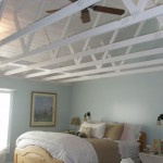 Remodeled master bedroom with decorative white beams, ceiling fan and bed as the focal decorative point
