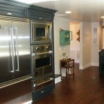 Blue kitchen cabinets with stainless steel appliances and hardwood floor