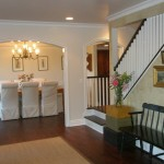 Interior remodel of English Country Cottage with white arch separating between dinning room area with white furniture and entrance area with dark brown floor, white and brown staircase and railing and brown bench