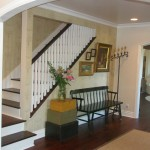 Interior Remodeled English Cottage entrance with brown and white stairway and wood bench