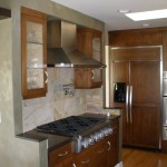 Kitchen with wall cabinetry stainless steel hood and stove and stone back-splash