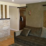 Partial living room view with wood floor stone work and accent wall