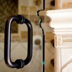 detail of shower door with bronze handle and a custom cut out