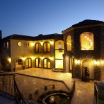 A tuscan style new home courtyard garden subtly lit with rustic lighting just after sunset sunset