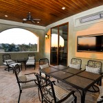 a luxurious balcony with an outdoor dining area and outdoor television