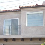 new stucco, windows and a sleek horizontal railing give this home a clean modern look