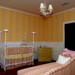 Kid room with stripes wall paper matching baby crib and love seat