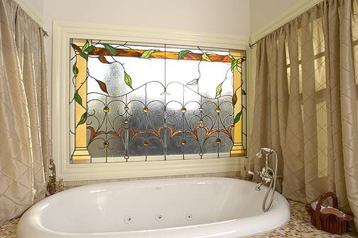 bathroom with white tub and wall window with decorative glass