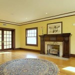 Remodeled living room area with hardwood floor, fireplace, crown and base molding and french door