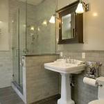 Mirror above Bathroom pedestal sink, shower with glass enclosure and stone tile work