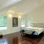 Bedroom with dark hardwood floors white decorative beams and decorative bed