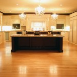 Overview of neoclassical kitchen with white cabinetry, kitchen island, hardwood floor and decorative chandeliers