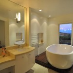 Modern bathroom with white cabinetry, white oval soaking tub and wall mirror