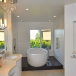 Modern bathroom with oval white soaking tub under large garden window