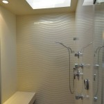 Modern enclosed shower with decorative wavy stone wall, stone bench and skylight