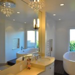 Modern bathroom with white cabinets white counter top wall mirror and modern light fixture