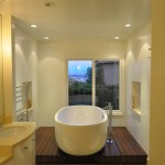 bathroom with white cabinetry, oval white tub sitting on wood stage and wall niche