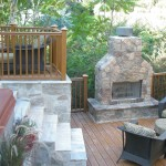 Outside patio with stone stairs and stone fireplace