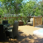 Wood deck with relaxation area with chairs and table surrounded by wood fence