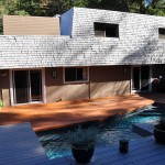 Renovated House exterior with stained concrete floor leading to pool and deck area
