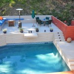 Overview of exterior pool with trex deck with sitting area and umbrella and redwood fence