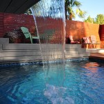 outside deck and Pool waterfall surrounded by redwood fence